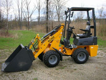 Mini front loader with barrel grapple for farming work