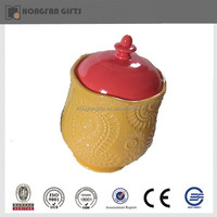 Yellow small porcelain jar with red lid