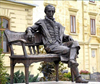 Famous garden bronze statue sitting on bench sculpture