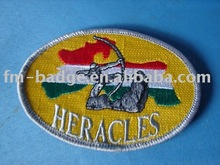 Wholesale OEM cheap custom Heracles design oval shape embroidery patches, merrowed/overlock heat press embroidered badge